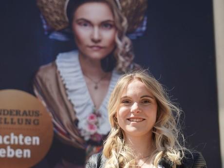 Anina Mond vor dem Stadtmuseum mit dem Plakat von ihr als Trachtenmodel